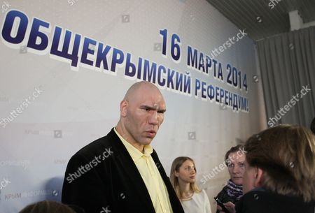 Russian Parliament Deputy Nikolai Valuev a Former Russian Heavyweight Professional Boxer Speaks to Journalists Near a Banner That Displays an Advertise For the Crimean Referendum in the City of Simferopol 750 Km South From Kiev 13 March 2014 Crimean Authorities Intend to Hold a Referendum on Sunday March 16 when Residents Will Be Asked if They Want to Split From Ukraine Ukrainian Government Denounced the Referendum As Being Illegal the Banner Reads: '16 March 2014 Referendum For All Crimean People' Ukraine Simferopol