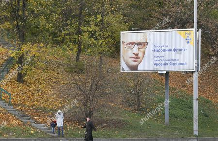 Ukrainians Walk in Front of a Pre-election Poster with a Portrait of Ukraine's Prime Minister Arseny Yatseniuk Leader of the People's Front Party in Kiev Ukraine 24 October 2014 the Parliamentary Elections in Ukraine Will Be Held on 26 October the Elections Are Supposed to Return Political Stability to the Crisis-hit Country But Few Observers Expect That They Will Facilitate a Peaceful Solution Ukraine Kiev