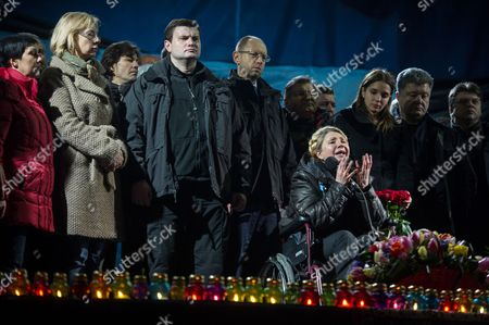 Stock Picture of Ukrainian Opposition Leader Yulia Tymoshenko (in Wheelchair) is Watched by Her Her Daughter Yevgenia (3-r) Ukrainian Fatherland Party Leader Arseniy Yatsenyuk (c with Glasses) and Other Unidentified Supporters As She Speaks to a Crowd at a Rally in Kiev Ukraine 22 February 2014 Former Ukrainian Prime Minister Yulia Tymoshenko on 22 February Appeared on the Stage of Kiev's Independence Square Or Maidan Hours After Being Released From Prison Tymoshenko who was in a Wheelchair First Praised the Protesters and Those who Were Killed During Last Week's Unrest 'The Heroes Never Die' She Said with a Tearful Voice the Square was Packed with Tens of Thousands of People the Former Ukrainian Prime Minister who was Sentenced to Seven Years in Jail For Abuse of Office in 2011 Earlier Said She Will Stand For President in May the Itar-tass News Agency Reported the Ukrainian Parliament on 22 February Set Early Presidential Elections For 25 May 2014 Ukraine Kiev