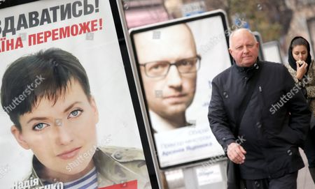 People Walk Past Pre-election Posters with Portraits of Nadia Savchenko (l) and Ukraine's Prime Minister Arseny Yatseniuk (c) Leader of Political Party People's Front in Kiev Ukraine 23 October 2014 Nadia Savchenko is an Officer of the Ukrainian Army who Fought As a Volunteer in the East of Ukraine in the Aidar Battalion and was Captured by Pro-russian Rebels the Parliamentary Elections in Ukraine Will Be Held on 26 October the Elections Are Supposed to Return Political Stability to the Crisis-hit Country But Few Observers Expect That They Will Facilitate a Peaceful Solution to the Bloody Conflict with Pro-russian Separatists Ukraine Kiev