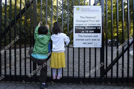 Six-year-old Zi Xuan (l) and Four-year-old Huang Yue Ran (r) Hang Onto the Gate of the Smithsonian National Zoological Park Just Before It Reopens to the Public After the End of the Sixteen-day Partial Shutdown of the Federal Government in Washington Dc Usa 18 October 2013 Congress Reached a Bipartisan Deal That Ended the Shutdown Late 16 October Which Allowed National Parks to Reopen and Furloughed Workers to Return to Work United States Washington