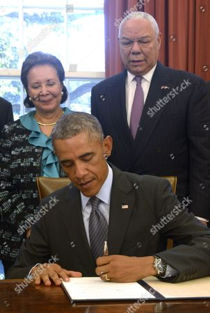 Us President Barack Obama with America's Promise Alliance Founding Chairman and Former Us Secretary of State General Colin Powell (r) and Current Board Chair Alma Powell (l) Signs the America's Promise Summit Declaration During a Ceremony in the Oval Office of the White House in Washington Dc Usa 22 September 2014 President Obama Will Be the Seventh Consecutive President to Sign the Declaration Which Calls on Americans to Help the Youth of America Reach Their Full Potential United States Washington