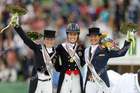 Britain's Rider Charlotte Dujardin (c) Celebrates on the Podium After Winning the Gold Medal in the Grand Prix Freestyle Dressage Competition During the World Equestrian Games 2014 in Caen France 29 August 2014 Seen Left Germany's Helen Langehanenberg Taking Second Place Silver Medal and Seen Right Dutch Rider Adelinde Cornelissen Taking Third Place Bronze Medal France Caen