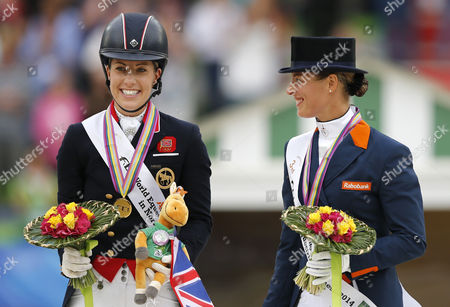 Stock Image of (l-r) Gold Medalist Charlotte Dujardin of Britain and and Dutch Bronze Medalist Adelinde Cornelissen Celebrates on the Podium After the Grand Prix Freestyle Dressage Competition During the World Equestrian Games 2014 in Caen France 29 August 2014 France Caen