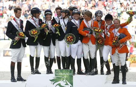 German Gold Medalists Sandra Auffarth Dirk Schrade Michael Jung and Ingrid Klimke (c) Britain's Silver Medalists William Fox-pitt Kristina Cook Zara Phillips and Harry Meade (l) and Dutch Bronze Medalists Elaine Pen Tim Lips Merel Blom and Andrew Heffernan (r) Celebrate on the Podium For the Team Classification of the Eventing Competition at the World Equestrian Games 2014 in Caen France 31 August 2014 France Caen