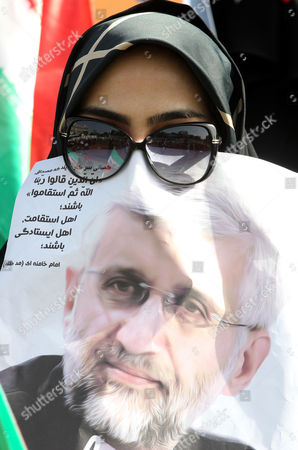 A Female Supporter of Iranian Presidential Candidate Saeed Jalili Covers Her Face with a Poster Depicting Jalili During an Election Campaign Rally in Tehran Iran 12 June 2013 Iran Will Hold Presidential Elections on 14 June 2013 Iran (islamic Republic Of) Tehran