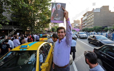 A Supporter of Newly Elected President Hassan Rouhani As Holds a Poster Depicting Him As He Takes Part in Street Festivities Right After the Official Announcement of His Victory in Tehran Iran 15 June 2013 Reformist Candidate Hassan Rouhani Has Won Iran's Presidential Election with More Than 50 Per Cent of Votes Interior Minister Mohammad Mostafa Najar Announced Rouhani Outclassed the Other Five Candidates Especially the Two Close to the Establishment: Hardliner Saeid Jalili and Conservative Ali-akbar Velayati Turnout in Friday's Vote was 72 Per Cent Observers Had Said That in Case of a High Turnout Rouhani Would Also Benefit From Protest Votes Iran (islamic Republic Of) Tehran
