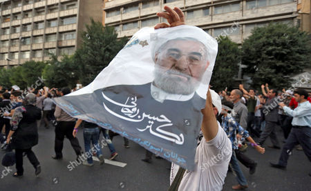 A Supporter of Newly Elected President Hassan Rouhani Holds a Poster Dipicting Him During Street Festivities Right After the Official Announcement of His Victory Tehran Iran 15 June 2013 Reformist Candidate Hassan Rouhani Has Won Iran's Presidential Election with More Than 50 Per Cent of Votes Interior Minister Mohammad Mostafa Najar Announced Rouhani Outclassed the Other Five Candidates Especially the Two Close to the Establishment: Hardliner Saeid Jalili and Conservative Ali-akbar Velayati Turnout in Friday's Vote was 72 Per Cent Observers Had Said That in Case of a High Turnout Rouhani Would Also Benefit From Protest Votes Iran (islamic Republic Of) Tehran
