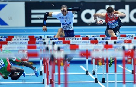 Rasul Dabo of Portugal (l) Tumbles and Falls As Pascal Martinot-lagarde of France (c) and Erik Balnuweit of Germany (r) Clear a Hurdle During Men's 60m Hurdles Event at the Athletics World Indoor Championships at Ergo Arena in Sopot Poland 08 March 2014 Poland Sopot