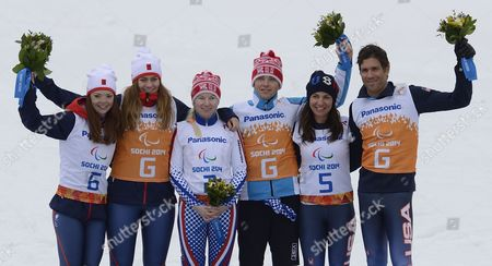 Gold Medalists Alexsandra Frantceva and Guide Pavel Zabotin (c) of Russia Bronze Medalists Danelle Umstead and Guide Robert Umstead (r) of the Usa and Silver Medalists Jade Etherington and Guide Caroline Powell of Grain Britain Celebrate on the Podium During the Flower Ceremony For the Women's Alpine Skiing Super Combined Run 2 Visually Impaired Race in Rosa Khutor Alpine Center at the Sochi 2014 Paralympic Games Krasnaya Polyana Russia 14 March 2014 Russian Federation Krasnaya Polyana