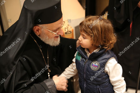 Gregory Iii Laham the Patriarch of Antioch and All the East with a Child on the Sideline of an Event Held at Dama Rose Hotel in Damascus Syria 17 December 2014 to Light the Christmas Tree at the Start of Charismas and New Year Celebrations in the War-torn Country Syrian Arab Republic Damascus