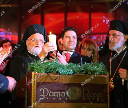 Gregory Iii Laham the Patriarch of Antioch and All the East (l) Lights a Candle For Syria on the Sideline of an Event Held at Dama Rose Hotel in Damascus Syria on 17 December 2014 to Light Christmas Tree at the Start of Christmas and New Year Celebrations in This War-torn Country Syrian Arab Republic Damascus