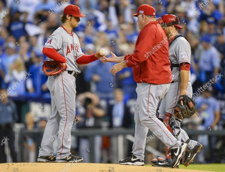 Los Angeles Angels Starting Pitcher C J Wilson (l) Hands the Ball to Los Angeles Angels Manager Mike Scioscia (r) After Giving Up a Three-run Double to Kansas City Royals Left Fielder Alex Gordon in the First Inning of Game Three of Their American League Division Series Mlb Playoff Baseball Game at Kauffman Stadium in Kansas City Missouri Usa 05 October 2014 United States Kansas City