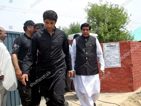 Stock Picture of Raja Pervaiz Ashraf (r) Former Prime Minister of Pakistan Ruling Party Pakistan People Party (ppp) Leaves Polling Station After Casting His Ballot During Parliamentary Elections in Gujar Khan Punjab Province Pakistan 11 May 2013 Millions of Voters Began Casting Their Ballots 11 May in Pakistan's Key General Elections After a Campaign Marked by Violence the Nationwide Vote Marks the First Time a Civilian Government Would Transfer Power to an Elected Successor After Completing a Full Five-year Term Pakistan Gujar Khan