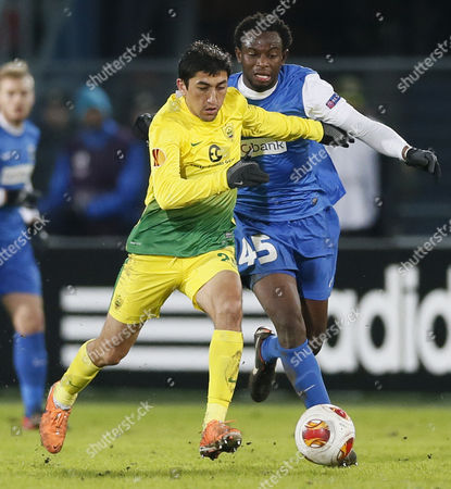 Odil Ahmedov (l) of Fc Anji Makhachkala Vies For the Ball with Bennard Kumordzi of Krc Genk During the Uefa Europa League Round of 32 First Leg Soccer Match Between Fc Anji Makhachkala and Krc Genk in Ramenskoye Outside Moscow Russia 20 February 2014 Russian Federation Ramenskoye