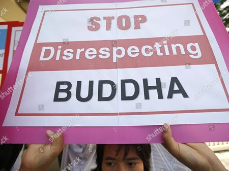 A Thai Buddhist Devotee Holds a Banner During a Protest Against the Art Exhibition Displayed a Disrespectful Fallen Buddha Sculpture in Front of the German Embassy in Bangkok Thailand 02 July 2013 Thai Buddhists Held a Protest Against the Outrage Over a Disrespectful Artwork of an Overturned Buddha Statue Displaying at the Viktualienmarkt Open-air Market in Munich Germany the Entitled 'Made in Dresden' and Created For the Project Series 'A Space Called Public' by Malaysian Artist Han Chong is Now Causing Debate Because Buddhists See the Sculpture As Violating a Religious Symbol Thailand Bangkok