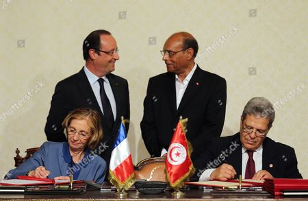 French President Francois Hollande (c-l) and His Tunisian Counterpart Moncef Marzouki (c-r) Stand Behind As French Minister For External Trade Nicole Bricq (l) and Tunisian Foreign Affairs Minister Othmane Jarandi (r) Sign a Treaty of Cooperation in Carthage Palace in Tunis Tunisia 04 July 2013 Hollande Arrived on a Two-day Official Visit to Tunisia Tunisia Tunis