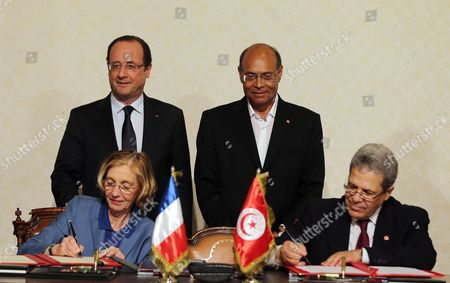 French President Francois Hollande (c-l) and His Tunisian Counterpart Moncef Marzouki (c-r) Look on As French Minister For External Trade Nicole Bricq (l) and Tunisian Foreign Affairs Minister Othmane Jarandi (r) Sign a Treaty of Cooperation in Carthage Palace in Tunis Tunisia 04 July 2013 Hollande Arrived on a Two-day Official Visit to Tunisia Tunisia Tunis