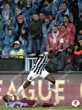 Juventus' Paul Pogba (top) Vies For the Ball with Trabzonspor's Jose Bosingwa During the Uefa Europa League Soccer Match Between Trabzonspor and Juventus Fc at Avni Aker Stadium in Trabzon Turkey 27 February 2014 Turkey Trabzon