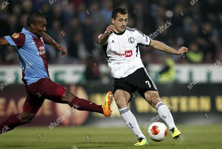 Legia Warsaw's Tomasz Jodlowiec (r) in Action Against Trabzonspor's Florent Malouda (l) During the Uefa Europa League Group J Soccer Match Between Trabzonspor and Legia Warsaw at Avni Aker Stadium in Trabzon Turkey 24 October 2013 Turkey Trabzon