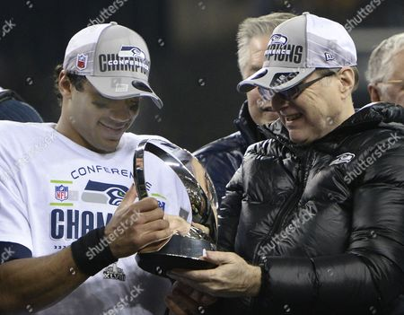 Seattle Seahawks Owner Paul Allen (r) Hands the George Halas Trophy to Quarterback Russell Wilson (l) After the Team Won Their Nfc Championship Playoff Game Against the San Francisco 49ers at Centurylink Field in Seattle Washington Usa 19 January 2014 the Seattle Seahawks Will Play the Afc Champion Denver Broncos in Super Bowl Xlviii at Metlife Stadium in East Rutherford New Jersey Usa 02 February United States Seattle