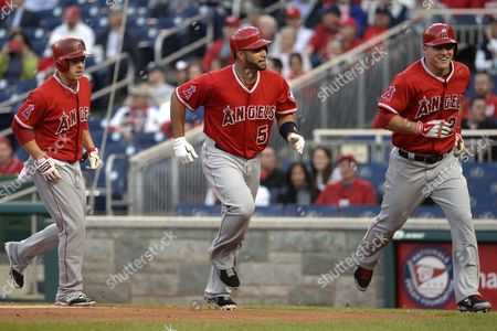 Los Angeles Angels Players First Baseman Albert Pujols (c) Center Fielder Mike Trout (r) and Left Fielder J B Shuck (l) Head Back to the Dugout After Crossing Home Plate Following Pujol's Three-run Homerun His 499th Career Homerun During the First Inning of the Mlb Game Between the Los Angeles Angels and Washington Nationals at Nationals Stadium in Washington Dc Usa 22 April 2014 United States Washington