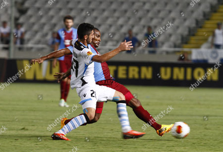 Florent Malouda (r) of Trabzonspor Vies For the Ball with Marios Stylianou (l) of Apollon Limassol During the Uefa Europa League Group J Match Between Apollon Limassol and Trabzonspor at the Gsp Stadium in Nicosia Cyprus 19 September 2013 Cyprus Nicosia