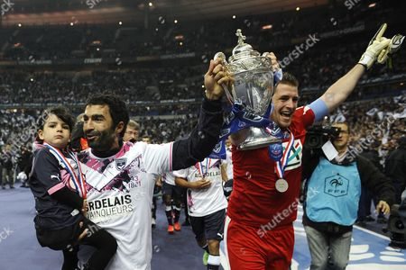 Bordeaux Goalkeeper Cedric Carrasso (r) and Player Benoit Tremoulinas (l) with His Daughter in His Arms Run with the Cup Toward Their Supporters After Their Victory Against Evian Thonon Gaillard During the Final of the French Soccer Championship Cup in Paris France 31 May 2013 France Paris