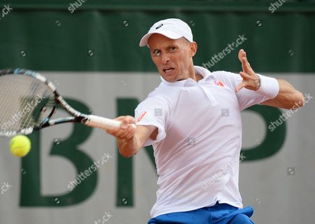 Stock Photo of Nikolay Davydenko of Russia Returns to Robin Haase of the Netherlands During Their First Round Match For the French Open Tennis Tournament at Roland Garros in Paris France 26 May 2014 France Paris