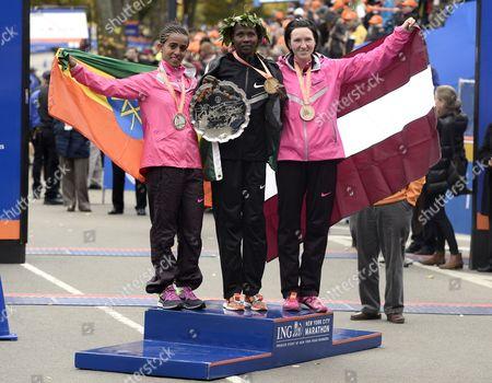 Winner Priscah Jeptoo of Kenya (c) Second Placed Buzunesh Deba of Ethiopia (l) and Third Placed Jelena Prokopcuka of Latvia (r) on the Podium After the New York City Marathon in New York New York Usa 03 November 2013 United States New York