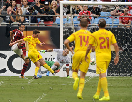 Fans React in the Background As Liverpool's Joe Allen (2-l) Takes a Shot For a Score Against Ac Milan's Goalkeeper Christian Abbiati (3-r) During the First Half of Their International Champions Cup Game at Bank of America Stadium in Charlotte North Carolina Usa 02 August 2014 Defending the Shot is Ac Milan's Adil Rami (l) Liverpool Beat Milan 2-0 United States Charlotte