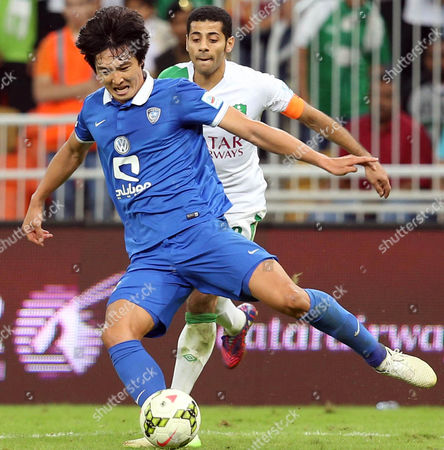 Kwak Tae-hwi (l) of Al-hilal Club in Action Against Taisir Al Jassim (r) of Al-hilal During the Saudi Professional League Soccer Match Between Al-ahli Club and Al-hilal Sc at King Abdullah Al Jawhara Stadium in Jeddah Saudi Arabia 21 February 2015 Saudi Arabia Jeddah