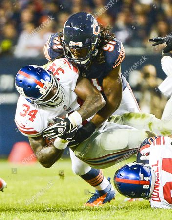 New York Giants Running Back Brandon Jacobs (l) Gains One Yard Before Being Brought Down by Chicago Bears Defensive End David Bass (r) in the First Quarter of Their Nfl Game at Soldier Field in Chicago Illinois Usa 10 October 2013 United States Chicago