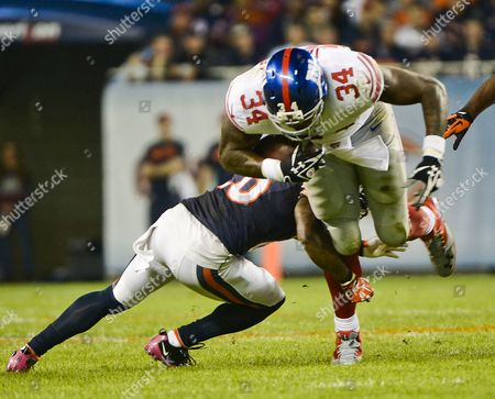 New York Giants Running Back Brandon Jacobs (r) Gains Seven Yards Running Before Being Stopped by Chicago Bears Cornerback Tim Jennings (l) in the First Quarter of Their Nfl Game at Soldier Field in Chicago Illinois Usa 10 October 2013 United States Chicago