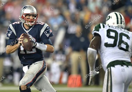 New England Patriots Quarterback Tom Brady (l) Scrambles As He is Pursued by New York Jets Lineman Muhammad Wilkerson (r) in the First Quarter of Their Nfl Game at Gillette Stadium in Foxborough Massachusetts Usa 12 September 2013 United States Foxborough