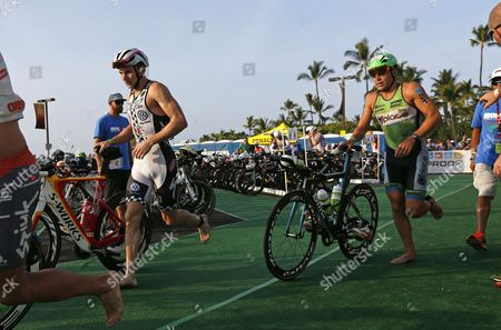 Ben Hoffman of the Usa and Bert Jammaer of Belgium Are out of the Water and Transitions to the Cycling Leg of the 2013 Ironman World Championship in Kailua-kona Hawaii Usa Early 12 October 2013 United States Kailua-kona