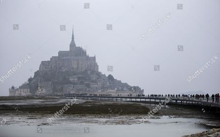 Low Tide Reveals Vast Expanses of Sea-bed Around the Mont Saint-michel in France 21 March 2015 This Year a Rare Confluence of Astronomical Factors is Prompting what Some in France Have Called the 'Tide of the Century ' and Driving Tourists to the Bay of Mont-saint-michel at Even High Numbers Than Usual Water Levels Are Expected to Reach 13 45 Metres High Higher Than a Four-story Building at Approximately 7:45 a M and 8 P M on 21 March and 8:30 a M and 8:50 P M on 22 March 2015 Due to Its Location Mont-saint-michel is One of the Places Most Vividly Affected by the Tides in All of Europe the Ocean Will Completely Cover a Low Bridge That Connects the Promontory to the Mainland 2 Kilometres Away France Mont Saint Michel