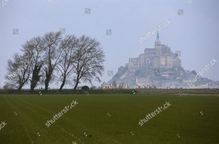 Morning Sun Illuminates the Mont Saint-michel in the Distance in France 21 March 2015 This Year a Rare Confluence of Astronomical Factors is Prompting what Some in France Have Called the 'Tide of the Century ' and Driving Tourists to the Bay of Mont-saint-michel at Even High Numbers Than Usual Water Levels Are Expected to Reach 13 45 Metres High Higher Than a Four-story Building at Approximately 7:45 a M and 8 P M on 21 March and 8:30 a M and 8:50 P M on 22 March 2015 Due to Its Location Mont-saint-michel is One of the Places Most Vividly Affected by the Tides in All of Europe the Ocean Will Completely Cover a Low Bridge That Connects the Promontory to the Mainland 2 Kilometres Away France Mont Saint Michel