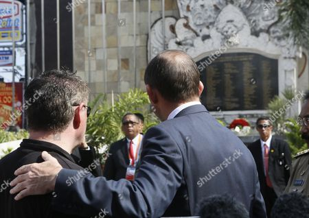 Stock Image of Australian Prime Minister Tony Abbott (r) Places His Arm on the Shoulders of Bali Bombing Survivor Australian Peter Hughes (l) As They Turn to Look at the Names of Victims at the Bali Bombing Memorial After Abbott Laid a Wreath at the Memorial to Those Killed in the 2002 Bali Bombing in Kuta Bali Indonesia 09 October 2013 There Were 202 People Killed in the Bombings Including 88 Australians Abbott Spoke to Media of His Experience in 2005 when He was in Bali with His Family During the 2005 Bali Bombings and He Ran Down to the Site and Then Spent the Day Helping out in the Hospital with Injured Indonesia Kuta