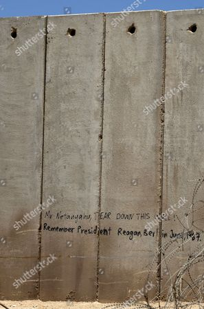 A Section of the Controversial Israeli 'Separation Barrier' Or Wall Inside the Shuafat Refugee Camp where Graffiti Equates what Former Us President Ronald Reagan Said About the Berlin Wall to Current Political Situation and Addressed to Israeli Prime Minister Benjamin Netanyahu in Shuafat West Bank 06 August 2013 on the Other Side of the Wall is the Sprawling East Jerusalem Neighborhood of Pizgat Ze'ev Which Many Consider a Jewish Settlement Israeli Media Report That Naftali Bennett Israel's Economy Minister Intends to Announce Tenders For Renewed Construction in East Jerusalem Soon Adding That He Hoped the Tenders Would Be Issued on a Large Scale Bennet Said in a an Interview 'We Insisted That There Be No Construction Freeze ' in Reference to the Agreement with the Palestinians Which Brought Israel and the Palestinian Authority Back to Renewed Direct Talks One Week Ago - Shuafat