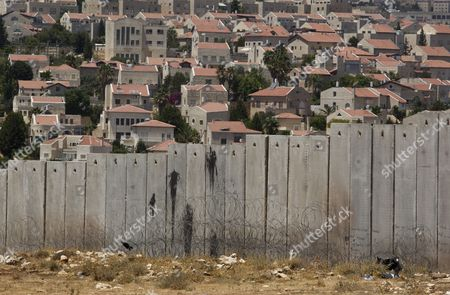 A View of the Israeli 'Separation Barrier Or Wall in the Shuafat Refugee Camp That Separates It From the Sprawling East Jerusalem Neighborhood of Pizgat Ze'ev (behind) Which Many Consider a Jewish Settlement in Israel 06 August 2013 Israeli Media Report That Naftali Bennett Israel's Economy Minister Intends to Announce Tenders For Renewed Construction in East Jerusalem Soon Adding That He Hoped the Tenders Would Be Issued on a Large Scale Bennet Said in a an Interview 'We Insisted That There Be No Construction Freeze ' in Reference to the Agreement with the Palestinians Which Brought Israel and the Palestinian Authority Back to Renewed Direct Talks One Week Ago Israel Pizgat Zeev