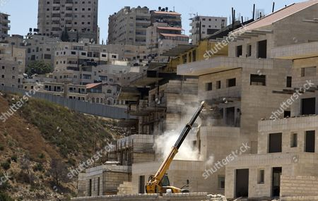 Palestinian Workers Dumping Material on a New Apartment Complex Being Finished Off in the Sprawling East Jerusalem Neighborhood of Pizgat Ze'ev Which Many Consider a Jewish Settlement in Israel 06 August 2013 Behind is the 'Separation Barrier ' Or Wall with the Palestinian Shuafat Refugee Camp on the Far Side Israeli Media Report That Naftali Bennett Israel's Economy Minister Intends to Announce Tenders For Renewed Construction in East Jerusalem Soon Adding That He Hoped the Tenders Would Be Issued on a Large Scale Bennet Said in a an Interview 'We Insisted That There Be No Construction Freeze ' in Reference to the Agreement with the Palestinians Which Brought Israel and the Palestinian Authority Back to Renewed Direct Talks One Week Ago Israel Pizgat Zeev