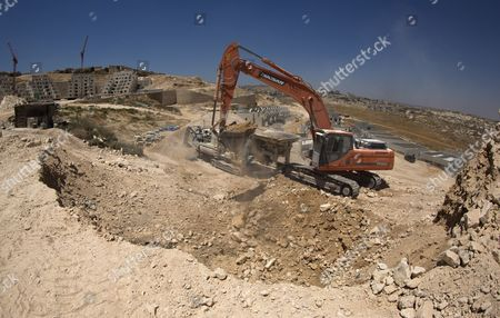 An Earth Mover Dumping Rocks Into a Crusher at a Large Building Site in the Sprawling East Jerusalem Neighborhood of Pizgat Ze'ev Which Many Consider a Jewish Settlement in Israel 06 August 2013 Behind is the West Bank Village of Hizme Israeli Media Report That Naftali Bennett Israel's Economy Minister Intends to Announce Tenders For Renewed Construction in East Jerusalem Soon Adding That He Hoped the Tenders Would Be Issued on a Large Scale Bennet Said in a an Interview 'We Insisted That There Be No Construction Freeze ' in Reference to the Agreement with the Palestinians Which Brought Israel and the Palestinian Authority Back to Renewed Direct Talks One Week Ago Israel Pizgat Zeev