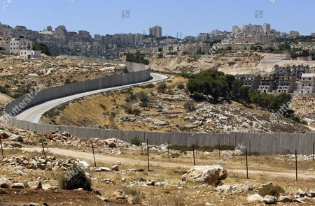 A View of the Israeli 'Separation Barrier Or Wall That Separates the Sprawling East Jerusalem Neighborhood of Pizgat Ze'ev (r) Which Many Consider a Jewish Settlement with New Apartment Complexes Nearing Completion From the Palestinian Shuafat Refugee Camp (l-above) Situated Just North of the Jerusalem Boundary in Israel 06 August 2013 Israeli Media Report That Naftali Bennett Israel's Economy Minister Intends to Announce Tenders For Renewed Construction in East Jerusalem Soon Adding That He Hoped the Tenders Would Be Issued on a Large Scale Bennet Said in a an Interview 'We Insisted That There Be No Construction Freeze ' in Reference to the Agreement with the Palestinians Which Brought Israel and the Palestinian Authority Back to Renewed Direct Talks One Week Ago Israel Pizgat Zeev