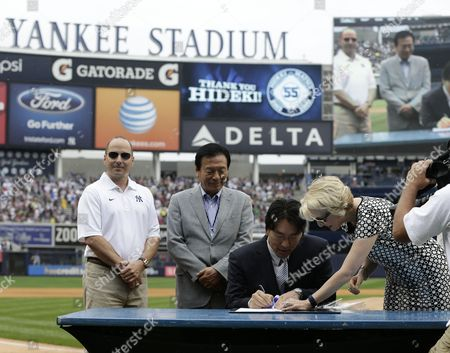 Former New York Yankee Hideki Matsui of Japan (c) is Seen Signing His Retirement Papers with the Yankees Organization Alongside Yankees Senior Vice President/assistant General Manager Jean Afterman (r) While His Father Masao Matsui (c-l) and Yankees Senior Vice President/general Manager Brian Cashman (l) Look on Before the Start of His Former Teams Game Against the Tampa Bay Rays at Yankee Stadium in the Bronx New York Usa 28 July 2013 United States Bronx