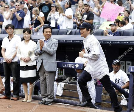 Stock Photo of Former New York Yankee Hideki Matsui of Japan (r) Runs out of the Yankees Dugout in Front of His Parents Father Masao Matsui and Mother Saeko Matsui and Brother Toshiki Before He Throws out the Ceremonial First Pitch After He Officially Signs His Retirement Papers with the Yankees Organization Before the Start of the Game Against the Tampa Bay Rays at Yankee Stadium in the Bronx New York Usa 28 July 2013 United States Bronx