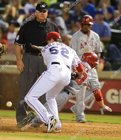 Stock Photo of Los Angeles Angels Player J B Shuck (r) Dives Back to First Base Safely After Being Caught Between Bases in the Eighth Inning and Texas Rangers Player Tanner Schppers (l) Drops the Ball at Rangers Ballpark in Arlington Texas Usa 30 July 2013 United States Arlington