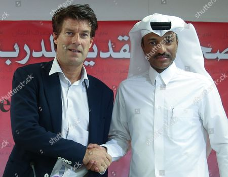 Newly Appointed Qatar's Lekhwiya Sports Club Soccer Head Coach Michael Laudrup (l) of Denmark Shakes Hands with Lekhwiya's Khalifa Khamis During a News Conference at the Press Centre of the Lekhwiya Sports Club Stadium in Doha-qatar on 02 July 2014 Qatar Doha