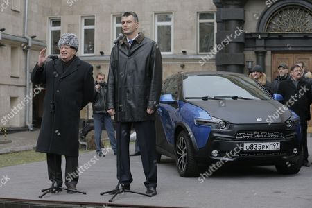 Stock Photo of Russian Billionaire and Owner of the Brooklyn Nets Basketball Team Mikhail Prokhorov (front R) Listens As Russian State Duma Vice Speaker and Leader of the Liberal Democratic Party of Russia Vladimir Zhirinovsky (front L) Speaks in Front of a Yo-mobile Urban Electric Crossover Car in Moscow Russia 01 December 2014 Mikhail Prokhorov Handed the Car's Keys Over to Vladimir Zhirinovsky During the Presidential Campaign 2012 While Taking Part in 'Duel' Televised Program of Russia 1 Tv Channel Presidential Candidate Mikhail Prokhorov Promised to Present Yo-mobile Car to His Contender Vladimir Zhirinovsky in Response to Zhirinovsky's Present a Wristwatch Russian Federation Moscow