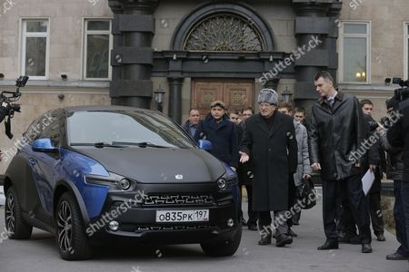 Stock Image of Russian Billionaire and Owner of the Brooklyn Nets Basketball Team Mikhail Prokhorov (front R) and Russian State Duma Vice Speaker and Leader of the Liberal Democratic Party of Russia Vladimir Zhirinovsky (front L) Stand Near a Yo-mobile Urban Electric Crossover in Moscow Russia 01 December 2014 Mikhail Prokhorov Handed the Car's Keys Over to Vladimir Zhirinovsky During the Presidential Campaign 2012 While Taking Part in 'Duel' Televised Program of Russia 1 Tv Channel Presidential Candidate Mikhail Prokhorov Promised to Present Yo-mobile Car to His Contender Vladimir Zhirinovsky in Response to Zhirinovsky's Present a Wristwatch Russian Federation Moscow